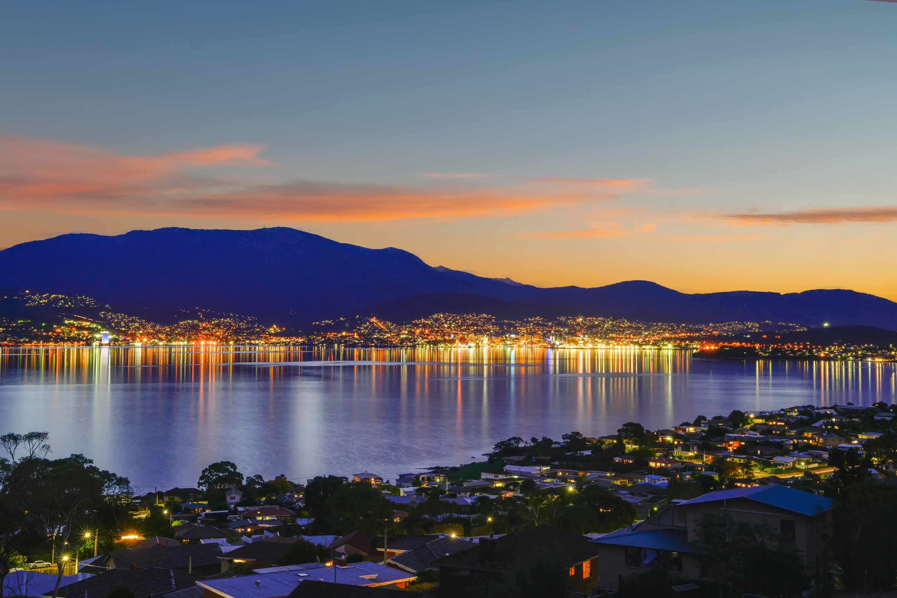 View looking across the River Derwent towards Hobart at night, with reflection of city lights on the water. Photo: Owen Fielding.
